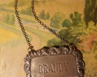 facny a drink - pewter brandy liqour bottle tag label, vintage antique barware, ornate design, neat piece for assemblage