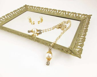 A Rectangular Mirrored Dresser Tray/Plateau -  Metal Detailing With Curves and Plumes Around the Edge - Paperboard Back w/Bumpers