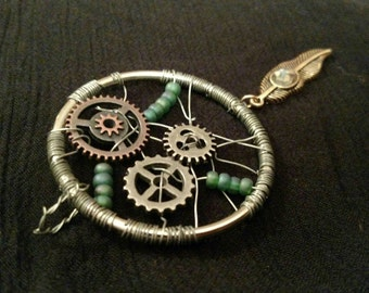 Dreamcatcher wire wrapped pendant with gears and feather charm.