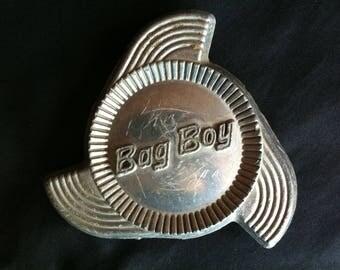 A Rusty Crusty Metal Emblem That Reads Bag Boy