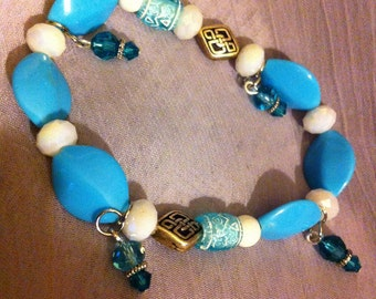 Aqua and white stretch beaded bracelet with Celtic knot beads.