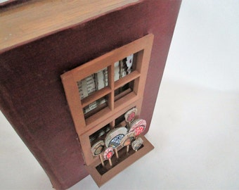 book sculpture with window and flowerbox