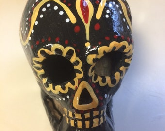Hand-painted papier-mâché sugar skull in black, gold, red