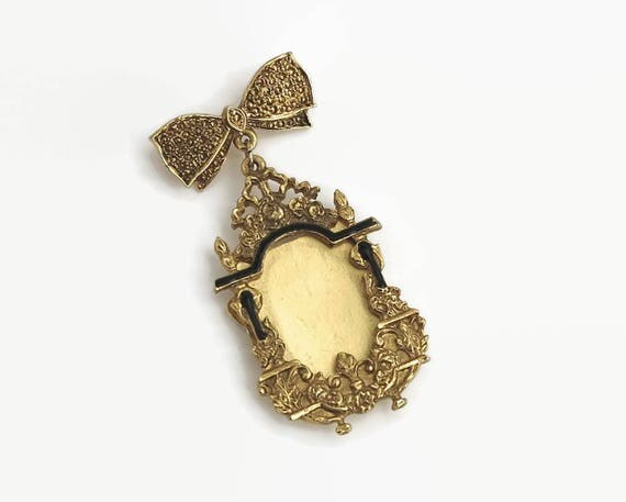 Large photo frame brooch, elaborate gold metal and black enamel frame hangs from gold metal bow, rollover clasp, Victorian revival, 1970s