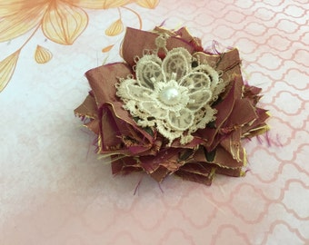 "Satin embroidered iridescent fabric flower with lace flowers in center. Pearl  center. 3"" approx."