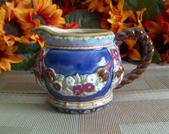 Nouveau Majolica Ceramic Pitcher. Has Floral Garland Design And Rope Handle. Wanjieng, China