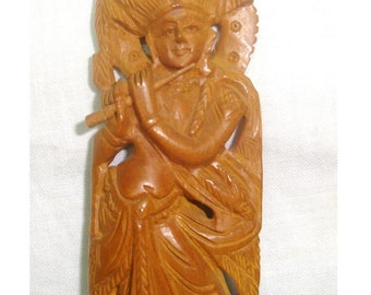 """Krishna, hand carved wood Hindu deity. 5.5"""" tall, beautifully detailed carving in good used condition. Carving is glued to a wooden base."""