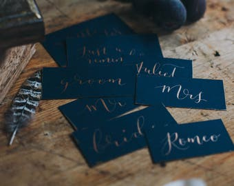 Navy flat place card featuring modern calligraphy hand lettered personalisation and handpainted edging