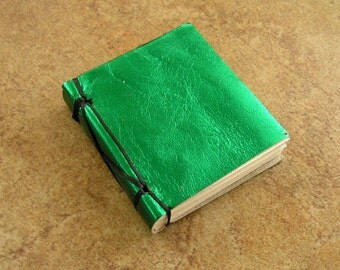 "Leather covered mini blank book, metallic green leather, hand laced, 3"" x 2 3/4"", 104 pages of vellum"