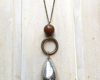 Long copper colored necklace with beaded pendant and large silver colored tear shaped bead