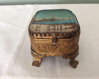 A Small Gold coloured Souvenir Trinket Box from the late 1800s, with a picture of Blackpool and the Tower, from the North Pier.