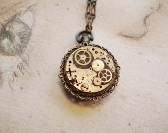 Small handmade steampunk pendant made of a little bronze colour watchcase, mecanism, gears , black resin, crystall resin,Black leather strap