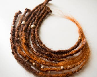 7(+2 extra) single real looking  brown into copper Dreadlocks. Crochet with beads.