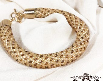 Bead crochet bracelet in tender beige and brown colors.  Gold plated accessory.