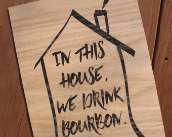 """Wood print """"in this house we drink bourbon"""""""