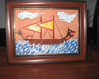 Handmade tooled leather art of a Viking ship at sea