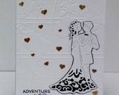 The World Is Yours Wedding card..Adventure awaits Wedding card...Embossed world background...White, black and gold...Wedding couple die cut!