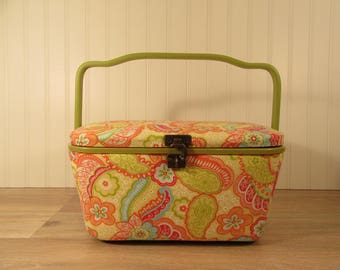 Fabric covered and plastic sewing basket with swing handle and hinged lid and clasp filled with sewing supplies