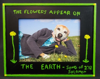 Flowers Appear on the Earth, folk art framed small canvas photograph of Boxer dog wearing clothes and sniffing dandelion flower