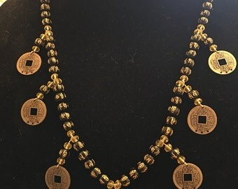 24 inch necklace, Asian themed, gold chain, black and gold beads with yellow crystals and gold Asian coins.