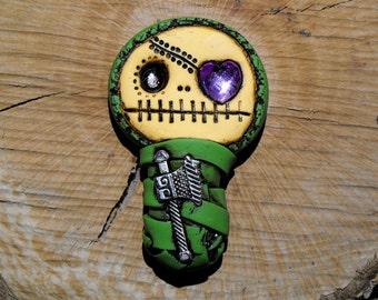Cute advocado green baby mummy. Adorable skull with a purple heart in his eye and a ax inside his body. Brooch or magnet