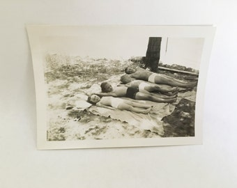 vintage black and white photo of kids on their backs at a picnic in swim suits laying out posing for camera