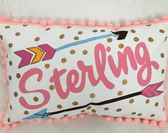 Pillow with gold polka dots and arrow accents, personalized name in pink