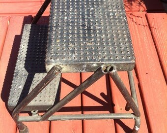 A Rusty Crusty Paint Splattered Heavy Industrial Style Metal Two Steps Stool With A Grated Appearance With Holes On The Top Of Both Steps