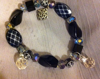 Black and crystal mix stretch beaded bracelet with Celtic knot charm.
