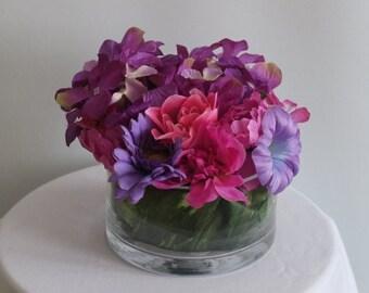 Purple floral arrangement centerpiece in round vase