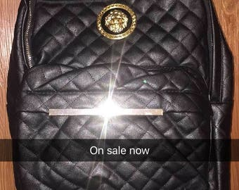 Quilted Black leather & Gold badge backpack