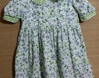 This little baby girl dress is too cute! Adorned with green leafy lilic flowers.