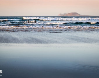 Picture of the beach at Famara at sunset with two surfers in the ocean, Lanzarote, Canary Islands.