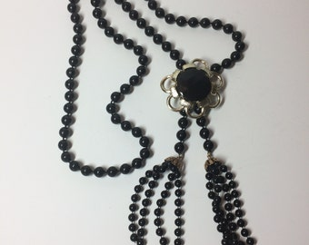 Long black bead necklace with flower pendant and tassels
