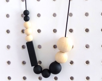 Arlo asymmetrical teething necklace, black silicone and wooden beads. Geometric, sensory ,fiddling, breastfeeding, baby wearing.