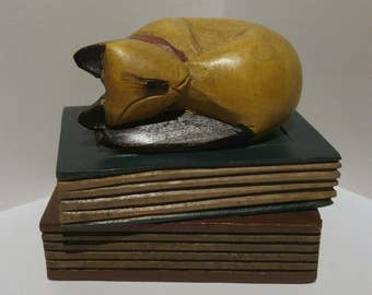 Hand carved wooden cat sleeping on stack of books