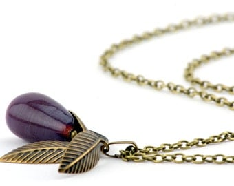 Long chain with drop of glass bead surrounded by delicate leaves
