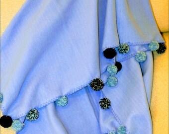 Lined light blue Pom Pom blanket.