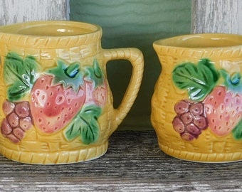 Yellow set measuring cups with strawberry and grapes