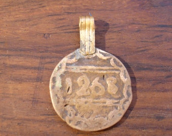 Moroccan very  tarnished old gold colour  coin with star and 1268 and brass bail or loop