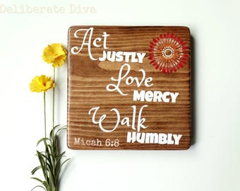 """7"""" x 7"""" solid wood signwith bible verse """"Act Justly Love Mery Walk Humbly"""" Micah 6:8 with white letters and red toned flower."""