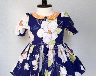 Blue Hawaii! Gorgeous white blooms cover this rich blue short-sleeved dress for a little girl. Size 6-12 mos.