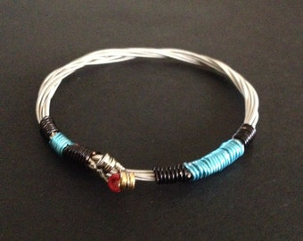 A handmade 3 String recycled guitar string bracelet/bangle