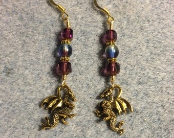 Gold dragon charm dangle earrings adorned with purple Czech glass beads.