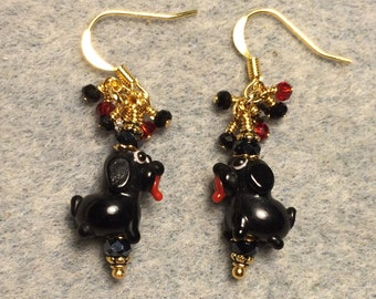 Tiny black lampwork puppy dog bead earrings adorned with black Chinese crystal beads and tiny dangling black and red Chinese crystal beads.