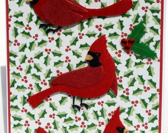 3D felt red cardinals layered on holly patterned paper with rhinestones.
