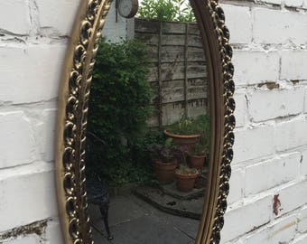 Gold oval mirror with lovely detail in the frame