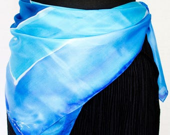 Foulard of blue turquoise color, painted by hand; is composed of two squares that intersect each other and complement each other