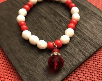 Red and white bracelet with red crystal dangle