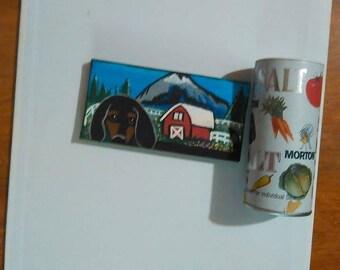 Miniature painting of a dachshund near a barn.